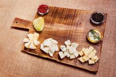 Bandeja do queijo decorada na placa de madeira rústica Imagem de Stock