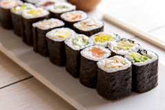 Bandeja do sushi do maki do alimento japonês mini na tabela de madeira branca Fotografia de Stock