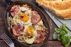 Bandeja dos ovos fritos com cebola, presunto e acelga fotografia de stock royalty free