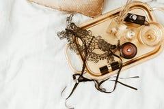 Bandeja elegante del oro y máscara negra en cama suave esencial plano de la mujer de la endecha por un día de fiesta Fotos de archivo libres de regalías