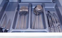 Bandeja gris con los cubiertos de plata en un cajón abierto de la cocina imagen fotografía de archivo