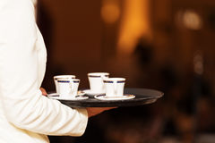 Bandeja levando do garçom com os copos de café em algum evento festivo Fotografia de Stock