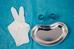 bandeja médica, guantes disponibles que muestran el signo de la paz, tarros para tomar el biomaterial alineado bajo la forma de c fotos de archivo