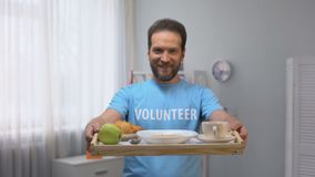 Bandeja masculina de sorriso de meia idade da exibição do voluntário com o café da manhã à câmera, cuidado filme