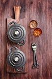 A bandeja pequena do ferro fundido com forquilhas e vidros em uma placa de corte Fotos de Stock Royalty Free