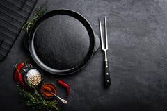 Bandeja vazia do ferro fundido com os ingredientes para cozinhar no fundo preto fotografia de stock