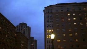 Bandejas da câmera ao prédio de escritórios genérico do tijolo na noite na cidade filme