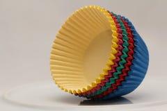 Bandejas de papel coloridas que cozem copos para queques e queques Imagem de Stock Royalty Free