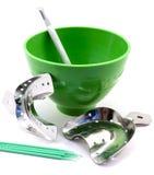 Bandejas dentais da impressão do metal, garrafa verde dental, espátula, pinos isolados fotos de stock royalty free