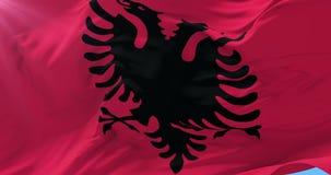 Bandera albanesa que agita en el viento con el cielo azul, lazo