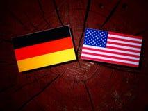 Bandera alemana con la bandera de los E.E.U.U. en un tocón de árbol Foto de archivo