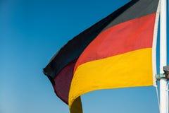 Bandera alemana en fondo del cielo azul Fotos de archivo libres de regalías