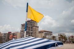 Bandera amarilla en la playa Foto de archivo libre de regalías