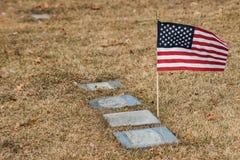 Bandera americana al lado de los sepulcros en el cementerio imagenes de archivo