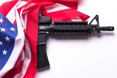 Bandera americana con el arma en el fondo blanco Imagen de archivo libre de regalías
