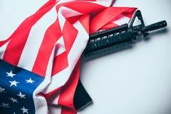 Bandera americana con el arma en el fondo blanco Imágenes de archivo libres de regalías