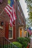 Bandera americana delante de casas americanas típicas Fotos de archivo libres de regalías