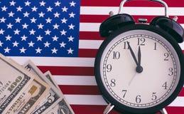 Bandera americana, despertador y dólares imagen de archivo