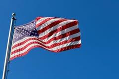Bandera americana en el aleteo del polo en el viento imagenes de archivo