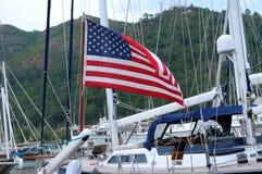 Bandera americana en un yate del palo en el puerto en un fondo del hil Fotografía de archivo libre de regalías