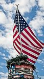 Bandera americana encima de un edificio con las luces del árbol de Navidad Fotografía de archivo libre de regalías