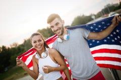 Bandera americana - la mujer y el hombre los E.E.U.U. se divierten la bandera de los E.E.U.U. del ganador del atleta que agita qu fotos de archivo