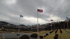 Bandera americana que agita en el aire del cementerio conmemorativo de la O.N.U en Busán, Corea del Sur, Asia almacen de metraje de vídeo