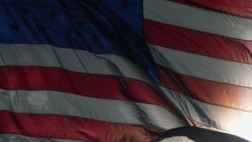 Bandera americana que renuncia en el cierre del viento para arriba almacen de video