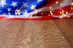 Bandera americana y guirnalda borrosas en la tabla de madera imagen de archivo libre de regalías