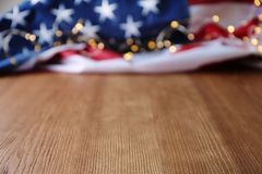 Bandera americana y guirnalda borrosas en la tabla de madera imagen de archivo