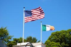 Bandera americana y bandera irlandesa que vuela de lado a lado foto de archivo