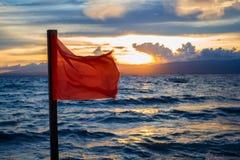 Bandera amonestadora de la playa que salpica en el viento Escena de la playa de la tarde con la señal de peligro del peligro Imagen de archivo libre de regalías