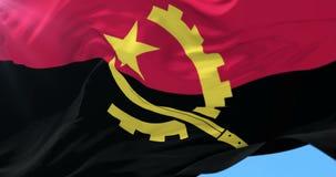 Bandera angolana que agita en el viento en lento con el cielo azul, lazo