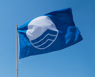 Bandera azul en la playa Imágenes de archivo libres de regalías