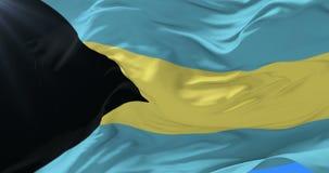 Bandera bahamense que agita en el viento en lento con el cielo azul, lazo