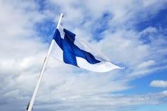 Bandera blanca con la cruz azul en fondo del cielo azul foto de archivo libre de regalías