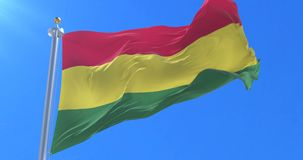 Bandera boliviana que agita en el viento en lento con el cielo azul, lazo