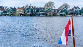 Bandera borrosa de los Pa?ses Bajos contra la perspectiva de un pueblo holand?s tradicional fotos de archivo