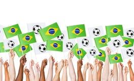 Bandera brasileña aumentada de la tenencia de brazos para el mundial Fotos de archivo libres de regalías