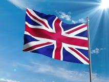 Bandera británica que agita en cielo azul con el sol Foto de archivo