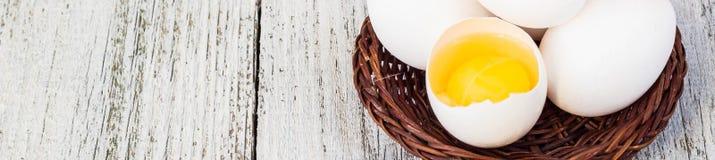 Bandera Broke un huevo entero entre los huevos blancos en cesta en un fondo blanco imagen de archivo libre de regalías