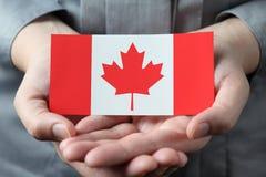 Bandera canadiense en palmas Imágenes de archivo libres de regalías