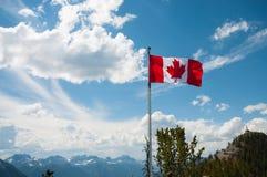 Bandera canadiense en pico de montaña Fotos de archivo libres de regalías