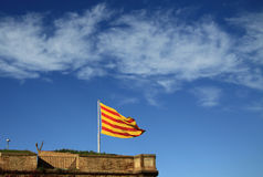 Bandera catalana que agita en el viento en el castillo de Montjuic Barcelona, Cataluña, España Foto de archivo