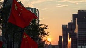 Bandera china de la cámara lenta que agita y que sopla en viento con puesta del sol en una calle metrajes