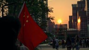 Bandera china de la cámara lenta que agita y que sopla en viento con puesta del sol en una calle almacen de video