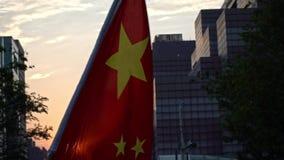 Bandera china de la cámara lenta que agita y que sopla en viento con puesta del sol en una calle almacen de metraje de vídeo
