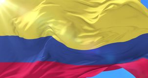 Bandera colombiana que agita en el viento en lento con el cielo azul, lazo