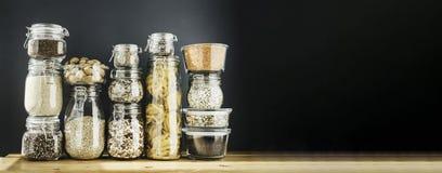 Bandera con el surtido de granos, de cereales y de pastas crudos en los tarros de cristal en la tabla de madera El cocinar sano,  fotos de archivo