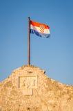 Bandera croata en la pared de la fortaleza sobre la entrada antigua Fotos de archivo
